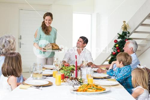 Mother serving Christmas meal to family