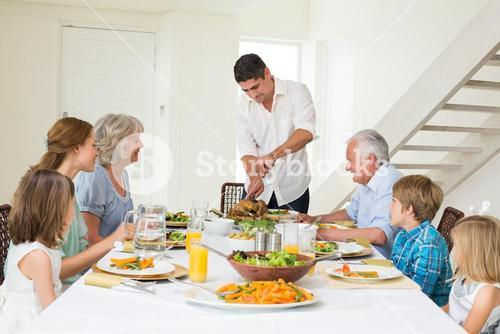 Father serving meal to family