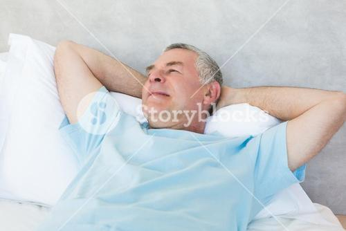 Senior man day dreaming in bed