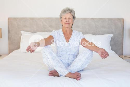 Senior woman meditating in bed