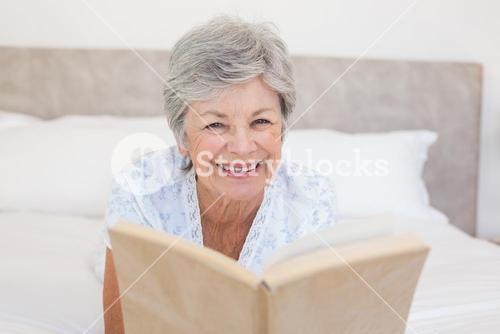 Happy senior woman reading story book