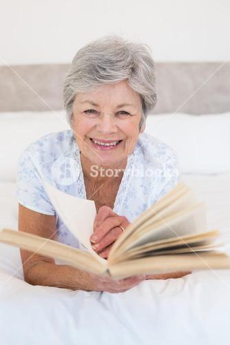 Senior woman turning story book pages