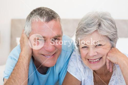 Senior couple smiling in bed