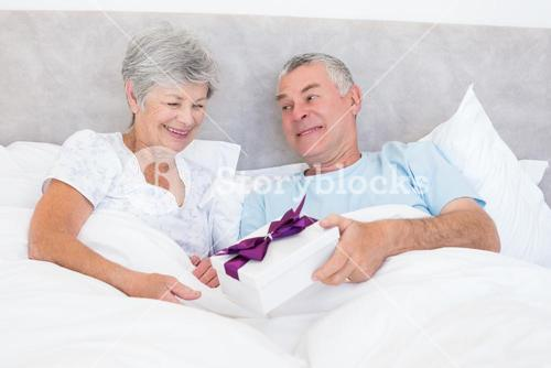 Senior man giving gift box to wife in bed