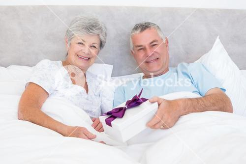 Senior man giving gift to wife in bed