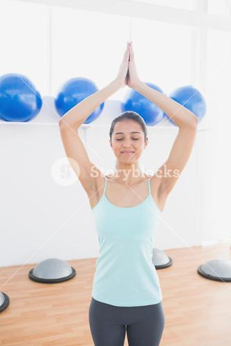 Sporty woman with joined hands in fitness studio