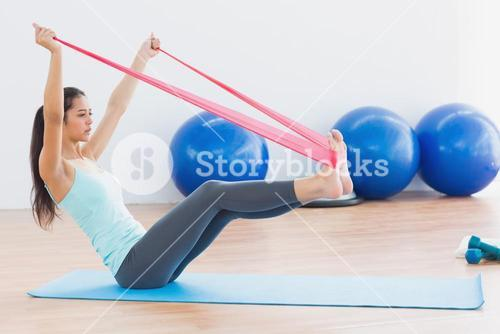 Sporty woman with exercise band in fitness studio