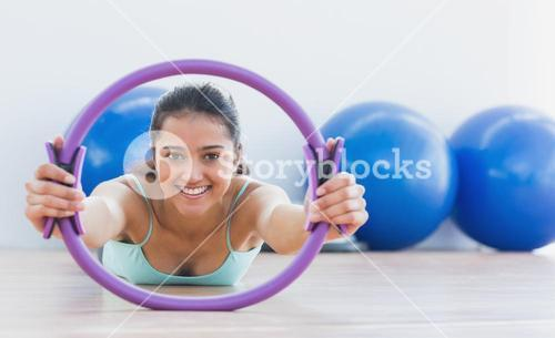 Smiling sporty woman with exercising ring in fitness studio