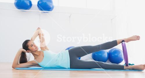 Sporty woman with exercising ring in fitness studio
