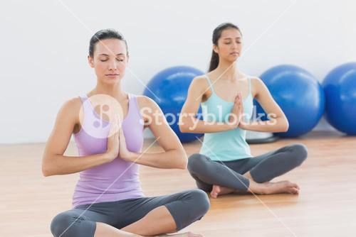 Two sporty women with joined hands in fitness studio