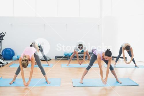 Sporty class doing pilate exercises in fitness studio