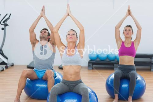 People with joined hands on exercise balls in gym