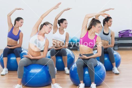 Sporty women stretching out hand on exercise balls at gym