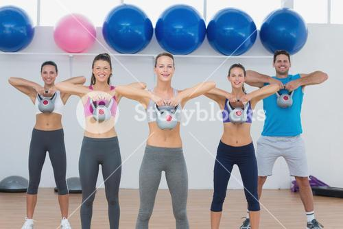 Fitness class exercising with kettlebells in gym