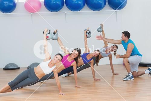 Instructor assisting fitness class with kettlebells