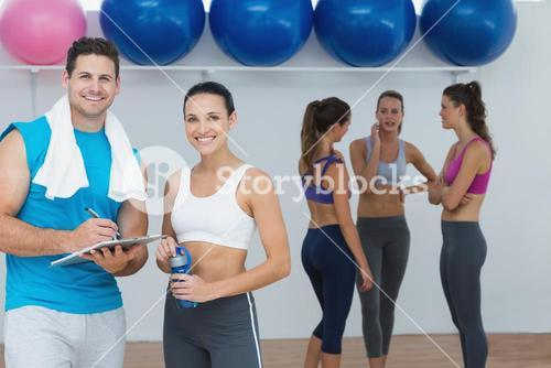 Smiling couple with fitness class in background