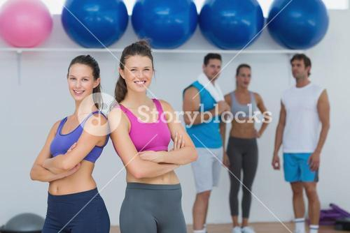 Fit women in sports bra with friends in background