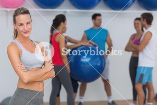 Fit young woman with friends in background at fitness studio