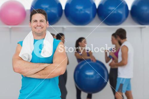 Smiling man with friends in background at fitness studio