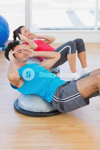 Young couple working out on dome balance