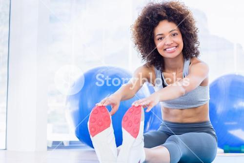 Sporty woman stretching hands to legs in fitness studio