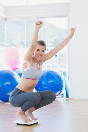 Fit woman cheering on scale in exercise room