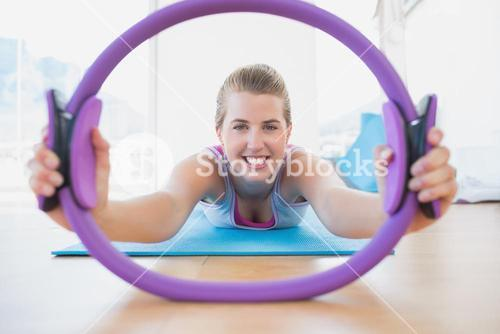 Smiling woman with exercising ring in fitness studio