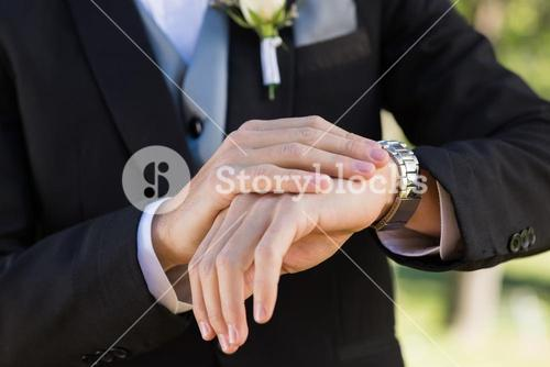 Midsection of groom checking time