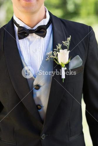Midsection of groom wearing boutonniere