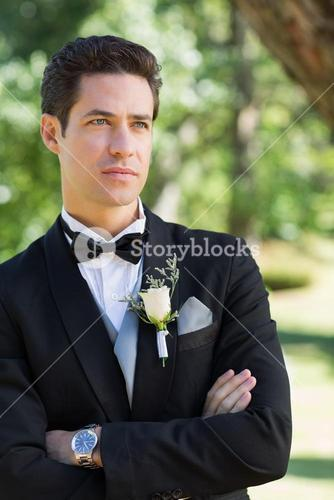 Thoughtful groom with arms crossed in garden