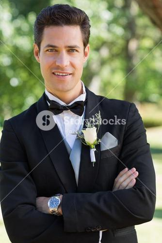 Confident groom with arms crossed in garden