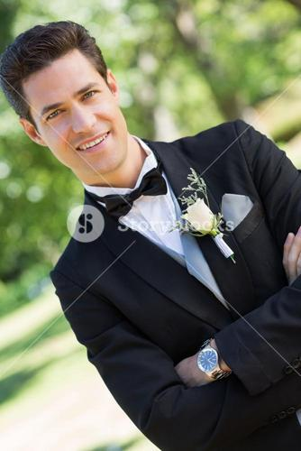 Confident bridegroom with arms crossed in garden