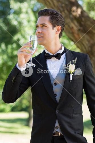 Thoughtful bridegroom drinking champagne
