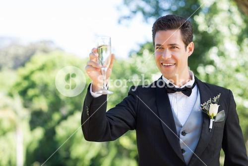 Groom toasting champagne flute in garden