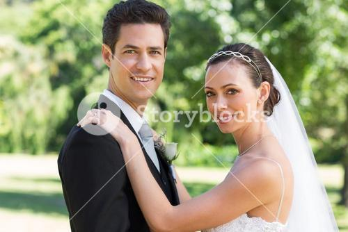 Bride and groom smiling in garden