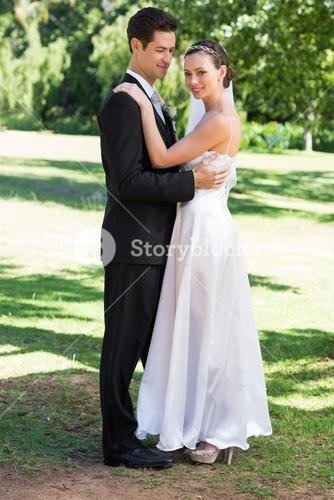 Young newly wed couple embracing in garden
