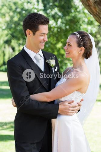 Newly wed couple embracing each other in garden
