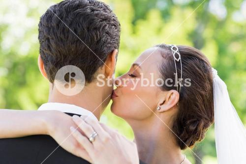 Young bride kissing groom on cheek