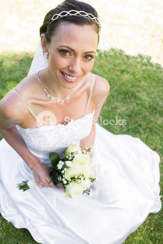 Bride holding flower bouquet while sitting on grass