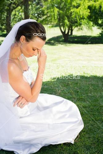 Female bride sitting on grass in park