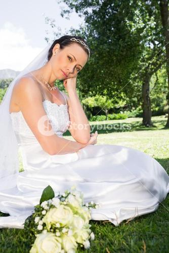 Sad bride with hand on chin in garden