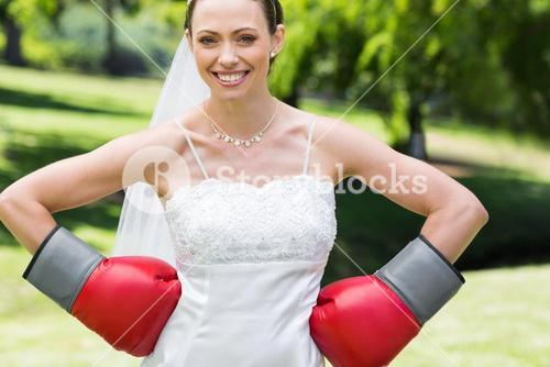Bride wearing boxing gloves with hands on waist