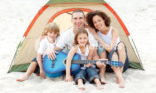 Family camping on beach playing a guitar