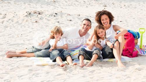 Family playing sitting on a beach