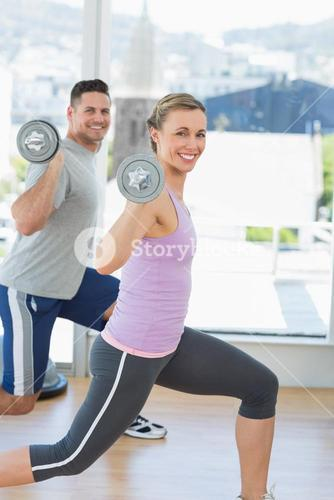 Happy woman and man exercising with barbells