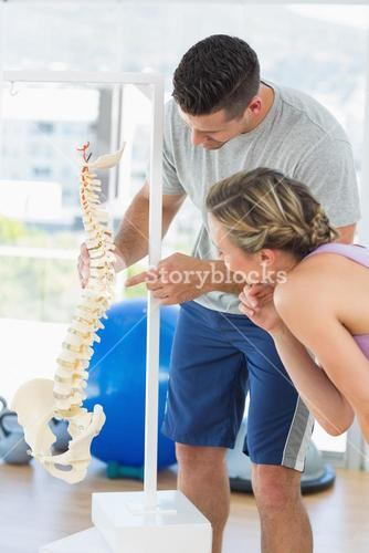 Instructor pointing on bone in the spine to woman