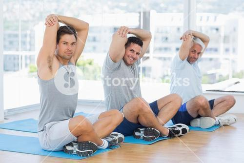 Men stretching on mats in fitness class