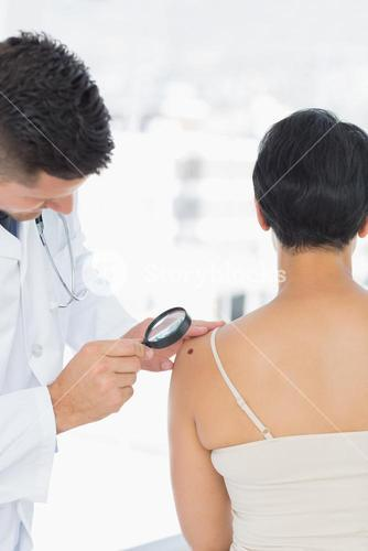 Dermatologist examining mole on woman