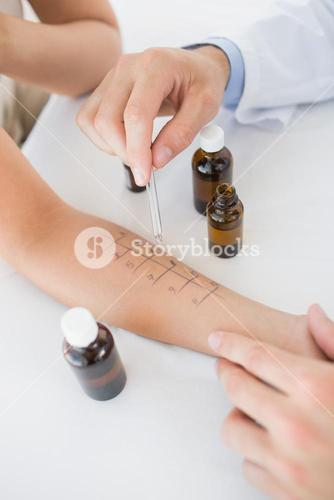 Doctor dropping medicine on hand of woman