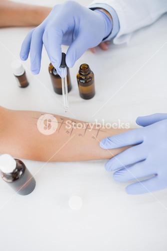 Doctor dropping medicine on hand of patient